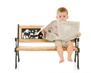 little boy reading a newspaper